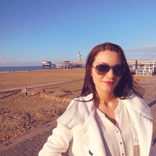 mulher com óculos escuros e sobretudo em praia holandesa