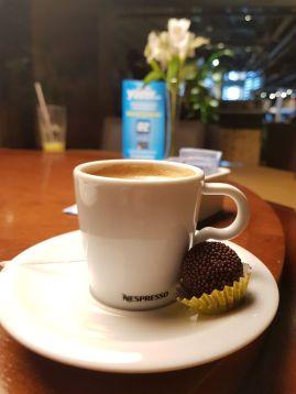 xícara de café e brigadeiro em mesa