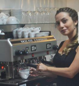 mulher jovem serve xícara de espresso direto da máquina