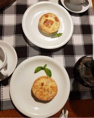 mesa com toalha xadrez, quiches e cafés