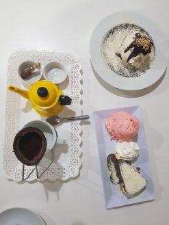 mesa composta por três pratos: um com café, outro com cheesecake de ninho e sorvete, outro com brownie e sorvete